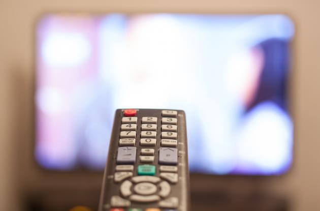 Fjernbetjening foran tv-skærm