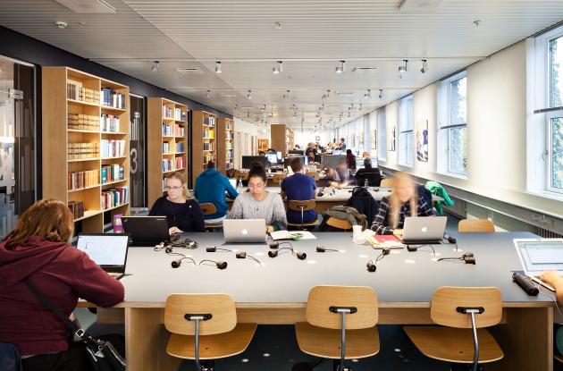 Studerende med laptops i biblioteksrum