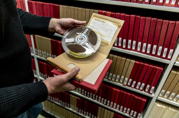 Employee presents reel-to-reel tape from Det Kgl. Bibliotek's collections