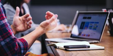 Person sidder foran laptop og notesbog og gestikulerer med hænderne