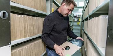 Employee among shelves with acetate discs