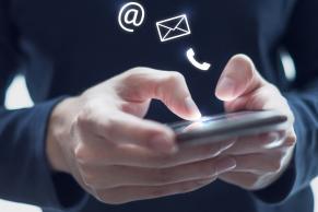 Hænder betjener mobiltelefon med kontaktsymboler